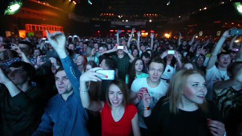 MOSCOW, RUSSIA - APR 05, 2014: Many people shout and photographed on phones in night club Stadium Live during Trancemission party of Radio Record
