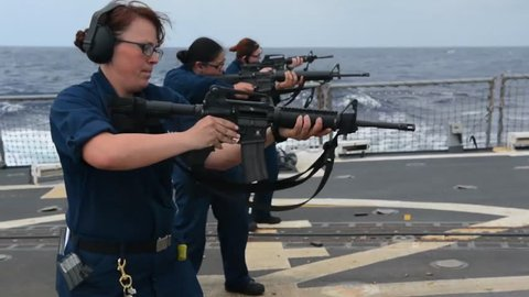 CIRCA 2010s - Navy women conduct live fire exercise on the deck of a warship.