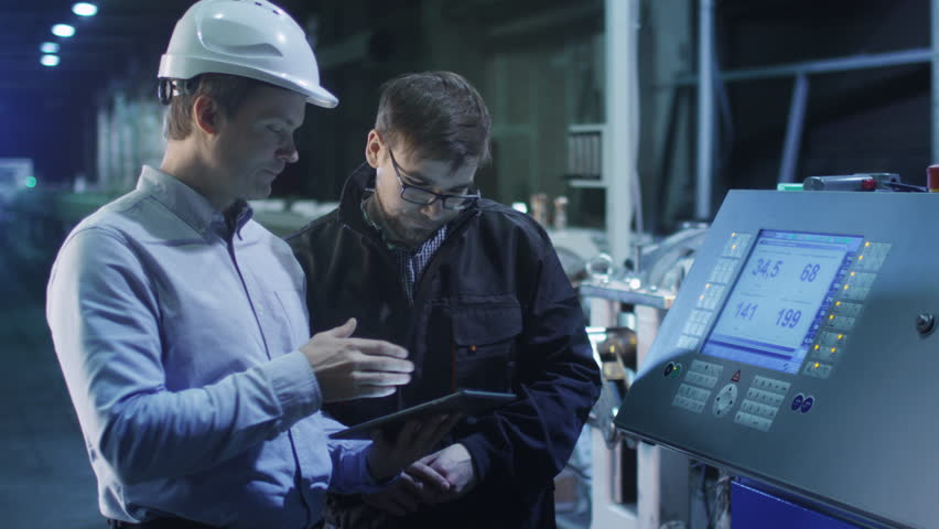 Engineer and Factory Worker are Setting Up CNC Lathe Machine Together. Shot on RED Cinema Camera in 4K (UHD). Its easy scale, rotate and crop without loosing quality.