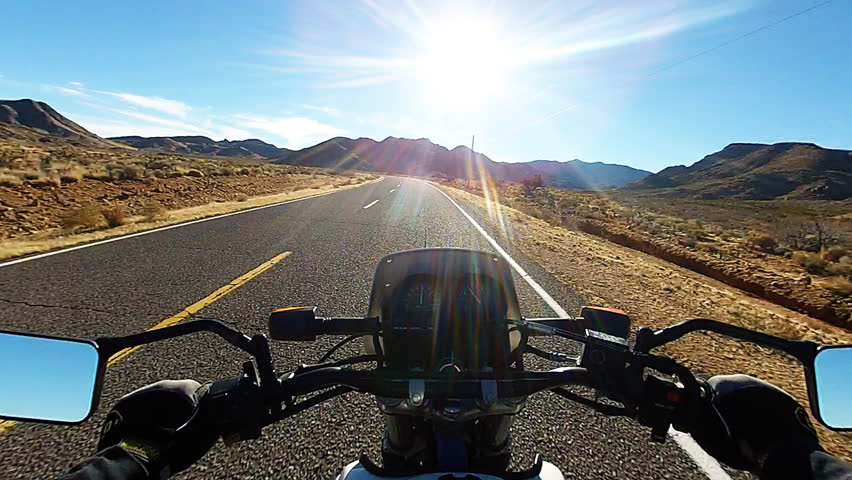Viewpoint or point of view of a motorcyclist riding into the sunset on a desert highway. An empty road provides a scenic view of a rugged desert landscape.