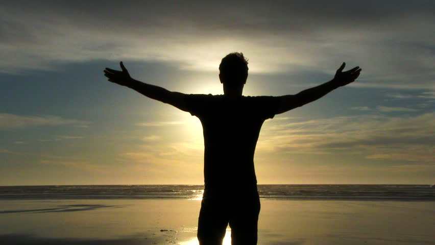 Model released person standing with arms up in the air on sandy beach shoreline catching some rays and enjoying the breeze at the Pacific Coast in Oregon.