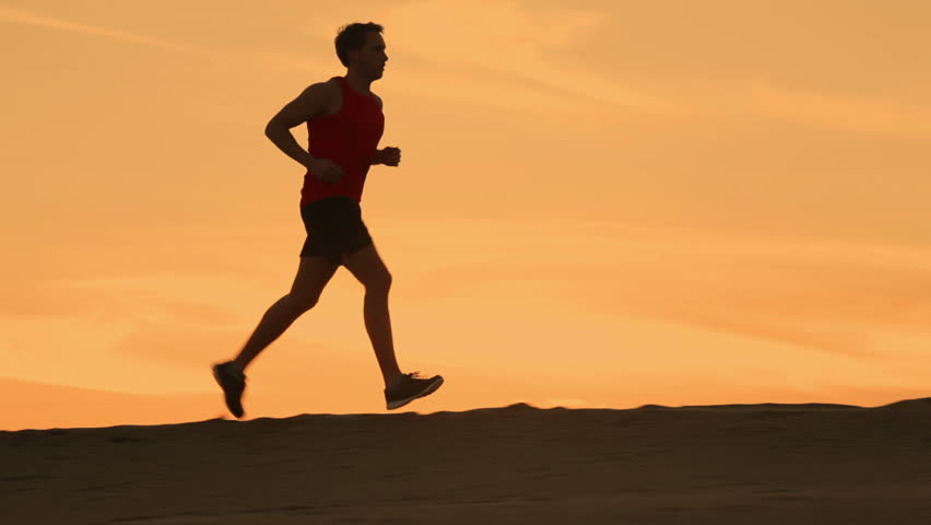 Running runner man jogging at sunset. Male jogger training for marathon run running up hill in silhouette against colorful yellow sky. Fit fitness model living healthy active outdoor lifestyle. | Shutterstock HD Video #9258596