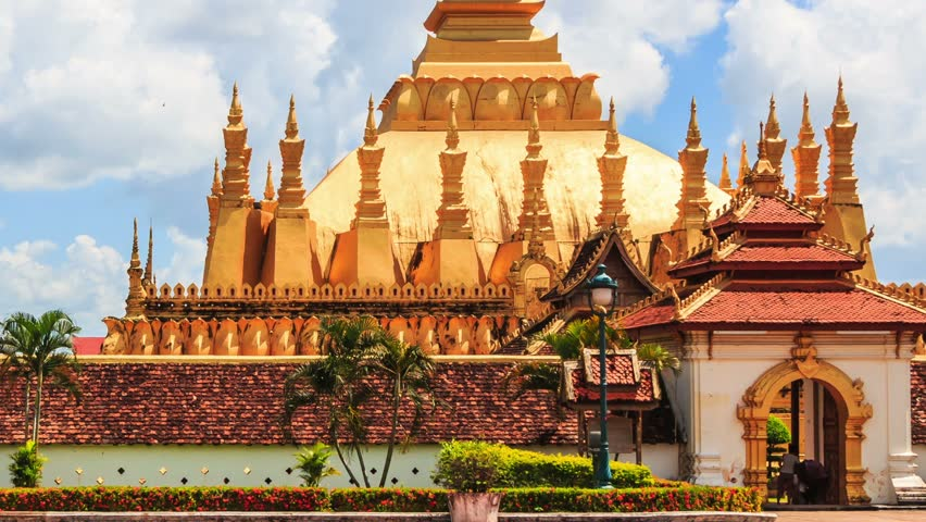 Genial Religious Architecture And Landmarks. Golden Buddhist Pagoda Of Phra That  Luang Temple Under Blue Sky
