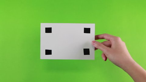 Hand of female put a white photo paper with black mark ( for tracking motion) on green screen background