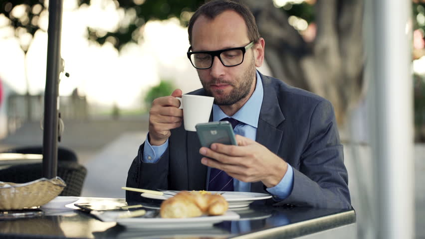 Young businessman using smartphone, drinking coffee in cafe in city