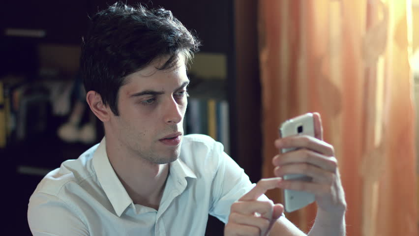 Pensive young man using cell phone to sand a message | Shutterstock HD Video #9335795