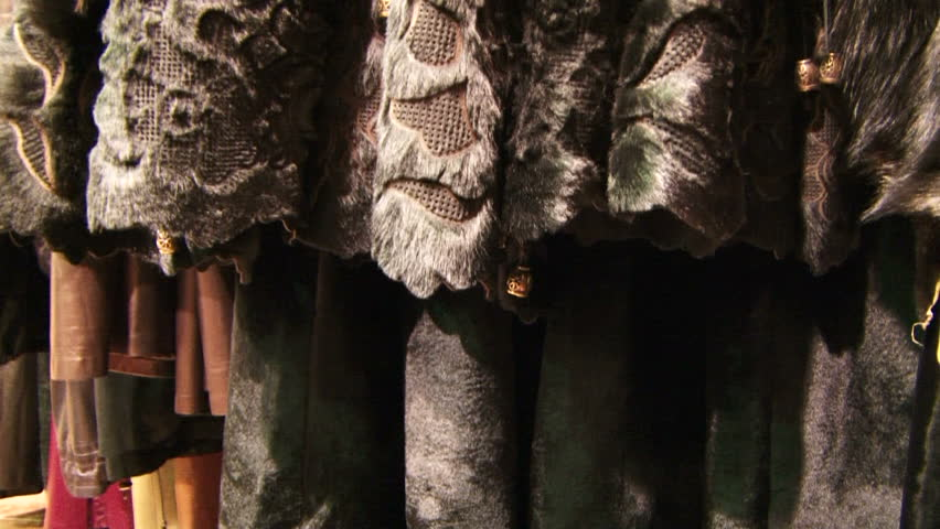 Fashion furs. Stylish clothing made of leather and fur hanging on a store shelf. Dolly/ Tracking shot