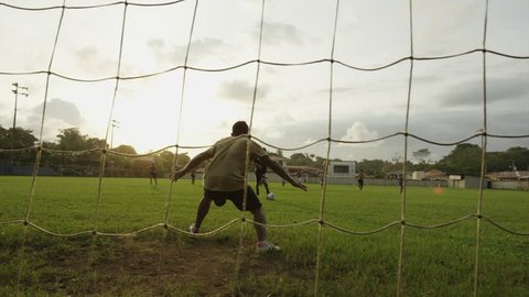 Low angle panning wide shot of soccer player scoring goal and cheering: Esterillos, Puntarenas, Costa Rica