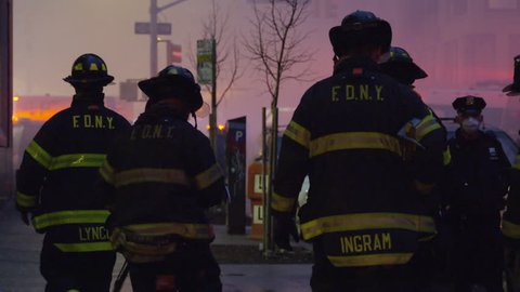 NEW YORK - MARCH 26, 2015: heroic FDNY firefighters walking toward fire, silhouetted, smoke, on the job in 4k, Manhattan NYC. FDNY responded to disaster; building collapse and fires in East Village.