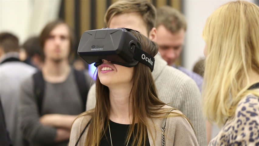 MOSCOW, RUSSIA - MARCH 29, 2015: Virtual reality game. Girl uses head mounted display Oculus Rift. Exhibition of modern technologies TechTrends Expo.
