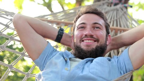 closeup video of young bearded caucasian man lying down and swinging in a hammock on a summer day