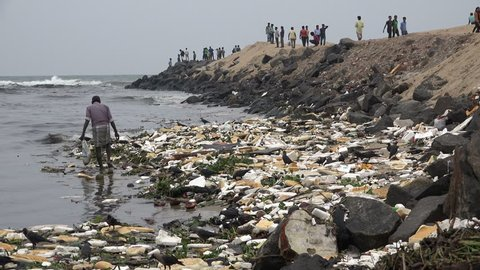 CHENNAI, INDIA - 28 NOVEMBER 2014: An unidentified man searches for items to be recycled on the shores of a beach, as tourists walk to and from a pier, in Chennai.