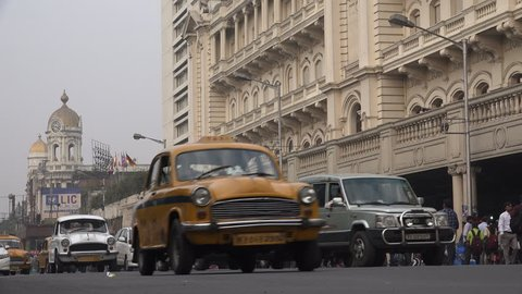 KOLKATA, INDIA - 13 DECEMBER 2014: Traffic drives past a colonial style building, currently used as a shopping mall, in Kolkata.