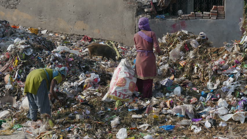 JAIPUR, INDIA - 21 OCTOBER 2014: Two unidentified women look for items to recycle at a garbage dump in Jaipur.