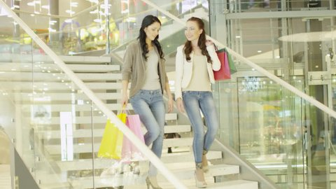 Two Girls with Shopping Bags are Moving Down The Stairs in Shopping Mall. Shot on RED Cinema Camera in 4K (UHD).