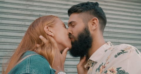 Hipster guy with a big beard kissing his happy girlfriend romantically in slow motion