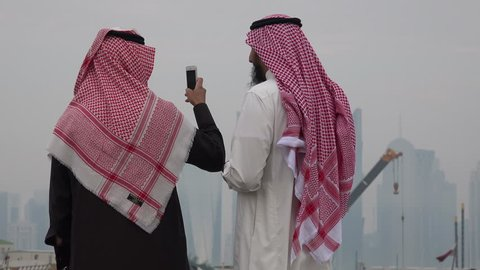 DOHA, QATAR - 17 JANUARY 2015: Two Saudi visitors take photos with their cellphone of the skyline in Doha, Qatar.