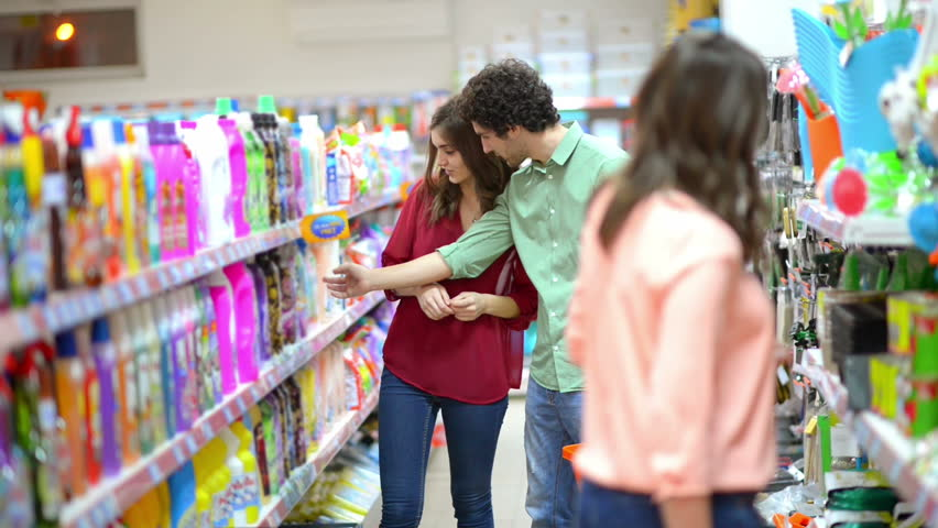 Happy woman showing to a man some cleaning product in supermarket | Shutterstock HD Video #9535505