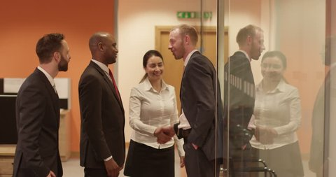 Group of multi-ethnic businessmen arrive to a business meeting in a modern glass conference room. In slow motion