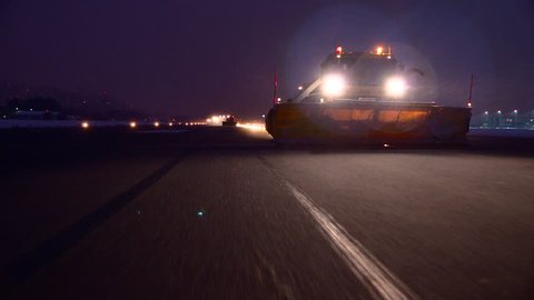 Machine removing snow off the runway of an airfield, by night, airport snow removal during storm, Innsbruck Airport, Austria, Europe