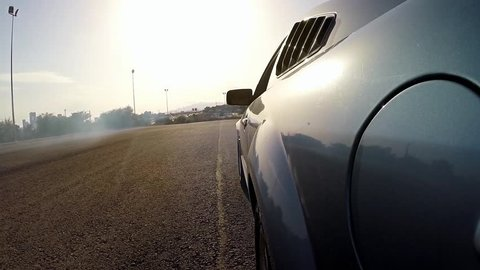 Powerful Muscle Car spinning into circles, making doughnut and burning tires - view from the side of a car fixed camera