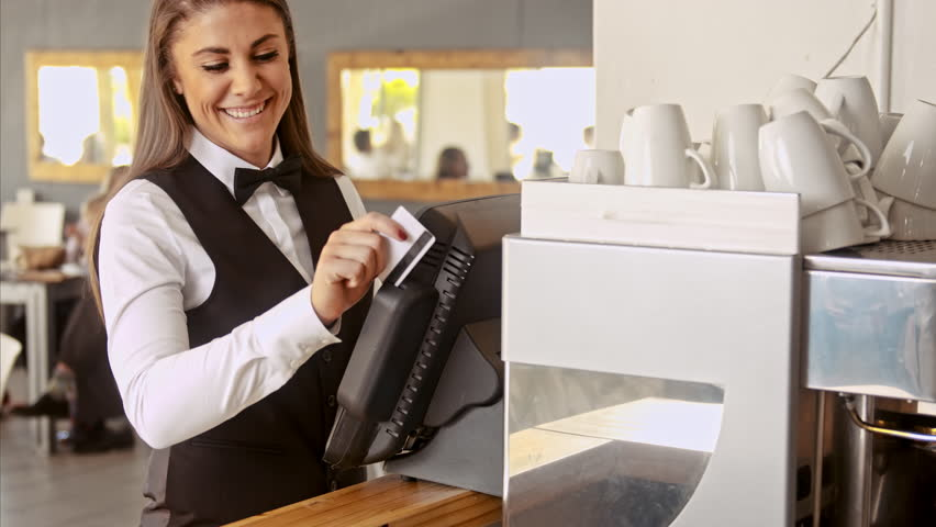 Wide shot of manager swiping touch payment terminal as waitress picking up table bill to service customer in restaurant/ coffee cafe.