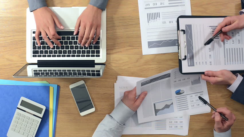 Business team working together at desk, a woman is typing on a laptop and men are examining financial reports, hands top view
