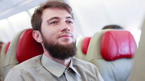 man relaxing on board on an airplane putting on earphones to listen to music