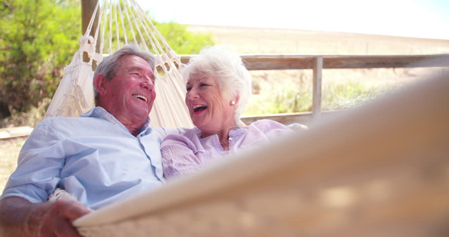 Slow motion video of a loving retired senior couple swinging in hammock and laughing together