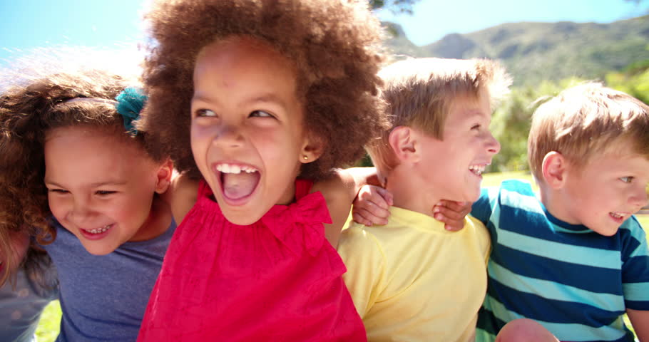 Happy mixed racial group of friendly children sitting in the sun laughing together, Panning in Slow Motion