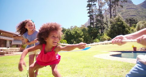 Little Afro girl having fun playing tug'o'war with friends in the garden in Slow Motion