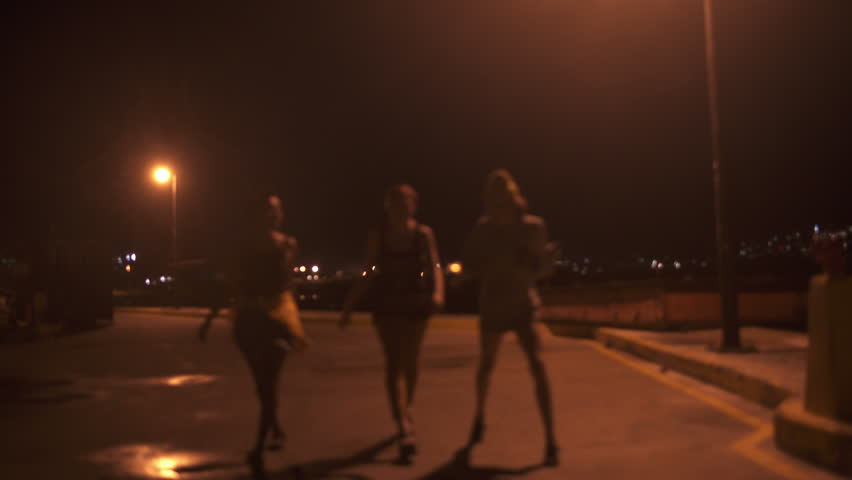 Silhouette of three teenaged grunge girls walking together under an orange street light