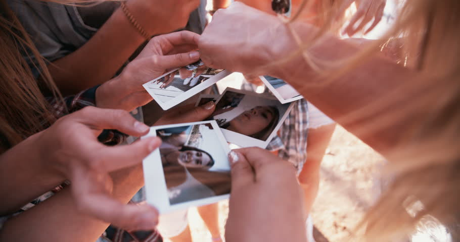 High angle shot of teen friends sharing instant photos of themselves having fun outdoors