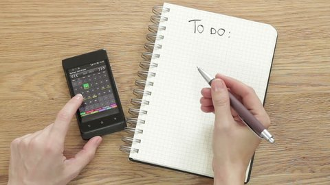 """Woman planning """"To do"""" list with smartphone calendar and notepad, top view"""