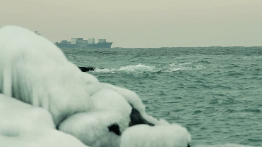 Foaming wave is breaking on the ice coverd stone. Cargo container ship sailing. | Shutterstock HD Video #9788645