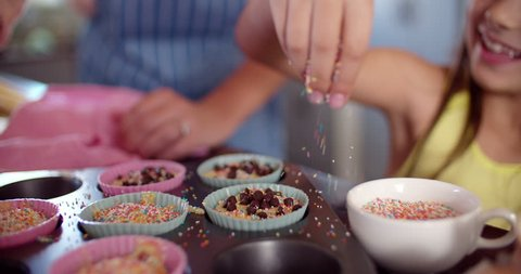 Cropped shot of the hans of a mom and daughter decorating cupcakes in a baking tray together, Panning in Slow Motion