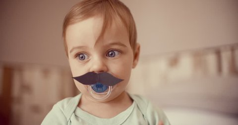 Sweet baby boy touching a paper moustache that's been stuck onto his pacifier