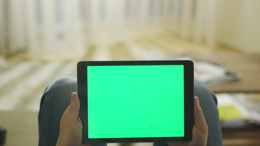 Man is Laying on Couch at Home and Holding Tablet with Green Screen in Landscape Mode on Lap. Shot on RED Cinema Camera in 4K (UHD). | Shutterstock HD Video #9798872