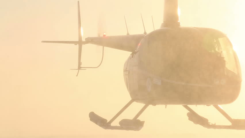 "ICE CAMP ""BARNEO"", NORTH POLE, ARCTIC - APRIL 10, 2015: Helicopters ""Robinson"" take to the skies on the background of the Arctic sun. 