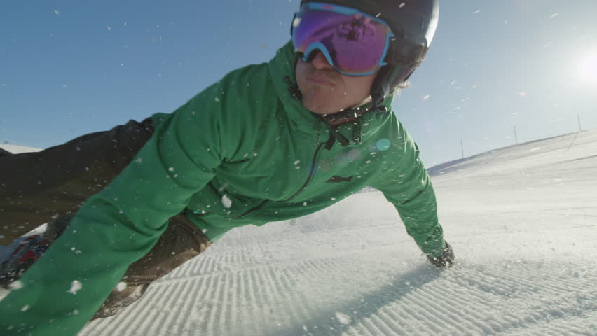 SLOW MOTION CLOSE UP: Snowboarder carving on perfectly groomed snow in mountain ski resort