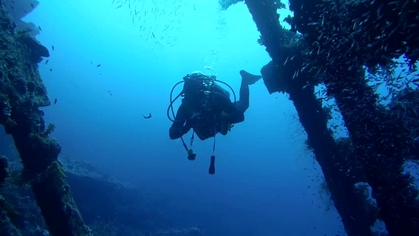 RED SEA, STRAIT OF GUBAL, EGYPT - OCTOBER, 2014:  A diver swims inside wrecked ship SS Carnatic, Red Sea, Egypt