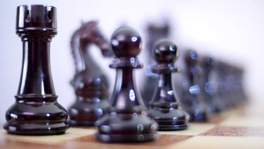 Chess Board and Pieces. Black lacquered pieces with defocused glare from lighting. Closeup. Shallow depth of field. Dolly shot. Follow focus