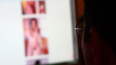 KIEV, UKRAINE, MAY 22, 2014: Man watching porno photos of naked women. Pornography may be presented in a variety of media, including books, magazines, photographs, sculpture, film, video, and other.