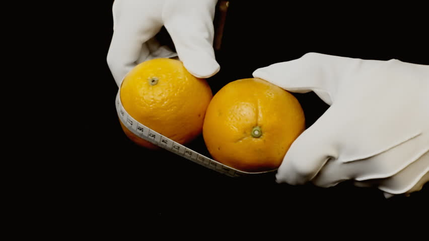 Measuring ripe oranges with a tailor's tape measure. Visual metaphor: checking the size of human anatomical parts.