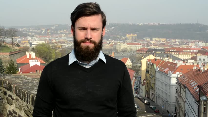young handsome man with full-beard (hipster) talks to camera and agrees - city in background
