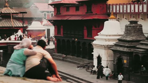KATHMANDU, NEPAL, CIRCA MAY 2014 - A couple rests at the ghats of the Pashupatinath Temple circa May 2014 in Kathmandu, Nepal. Pashupatinath Temple is one of the most sacred Hindu temples of Nepal.