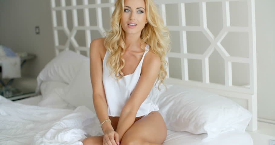359c1ba2bdc Sexy Young Woman Wearing Lingerie Sitting on White Bed with Elbow on her  Knee and Hand Touching her Long Blond Hair.