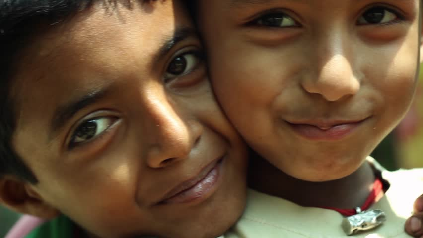Two Indian village boys smiling and posing for the camera closeup