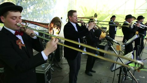 """MOSCOW, RUSSIA - MAY 09, 2015: trombones and trumpets. Brass Band performing on the stage in the park. Festival marching bands in the city park """"Muzeon."""""""