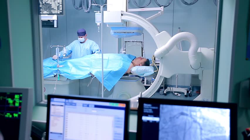 In an operation room a surgeon and a nurse make a surgery. The surgery is being controlled via monitors.